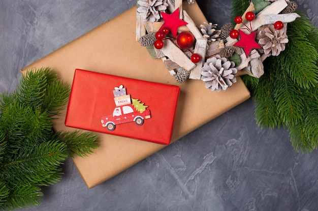 Christmas composition. gift box, fir tree, wooden toy car with santa and text x-mas. concept. flat lay, copy space