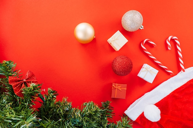 Christmas composition. gift box, firtree branches, xmas candies, red festive decorations on red background. copy space.