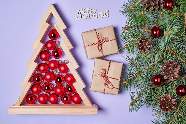 Christmas composition of gift boxes and wooden christmas tree with red christmas balls inside