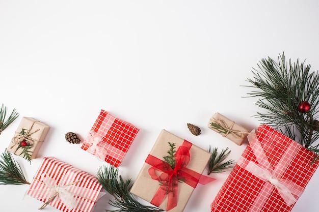 Новогодняя композиция. подарок, рождественские украшения, ветки кипариса, сосновые шишки на белом фоне