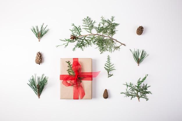 クリスマスの作文。ギフト、クリスマスの装飾、ヒノキの枝、白い背景の上の松ぼっくり