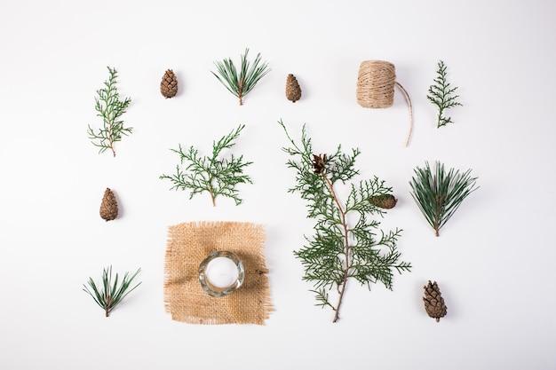Новогодняя композиция. подарок, новогоднее украшение, ветки кипариса, сосновые шишки на белом
