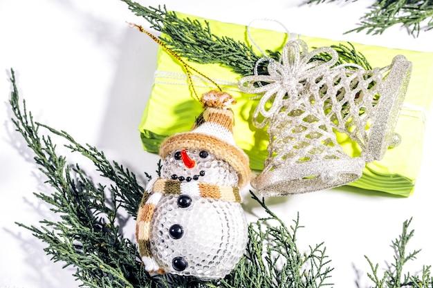 クリスマスの構成ギフトモミの木の枝と黄色のギフトボックスに雪だるまの白い装飾