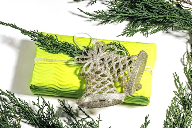 クリスマス作文。ギフト、モミの木の枝、黄色のギフトボックスに銀の鐘の装飾。クリスマス、冬、新年のコンセプト。