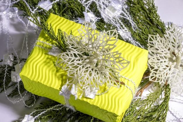 クリスマス作文。ギフト、モミの木の枝、黄色のギフトボックスに白い装飾。クリスマス、冬、新年のコンセプト。