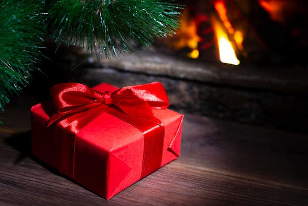 Christmas composition, gift under the tree near a burning fireplace, close-up