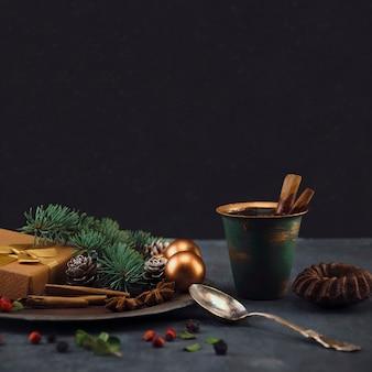Новогодняя композиция подарок с игрушками чашка кофе с корицей и шоколадный маффин на столе