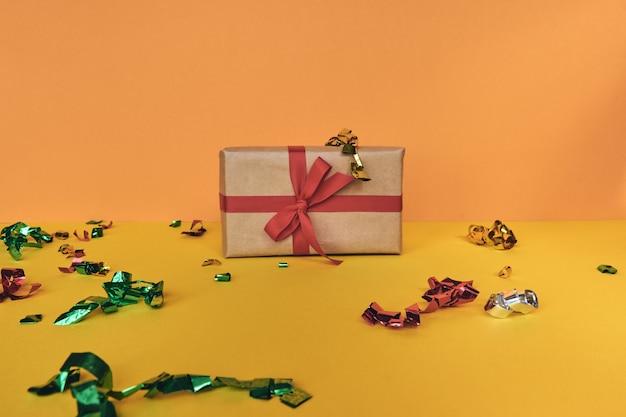 크리스마스 구성입니다. 파스텔 종이 화려한 배경에 빨간 리본과 색종이 조각 장식이 있는 giftbox. 크리스마스, 겨울, 새 해 축 하 개념입니다. 평평한 평지, 평면도, 복사 공간