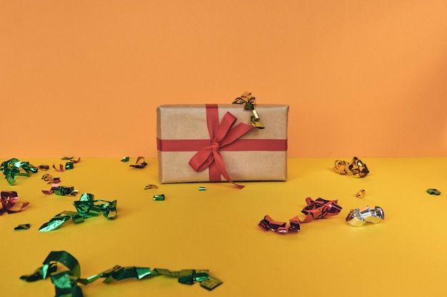 Christmas composition. giftbox with red ribbon and confetti decorations on pastel paper colorful background. christmas, winter, new year celebration concept. flat lay, top view, copy space
