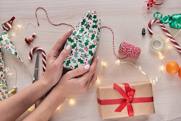 Christmas composition. giftboxes, presents wrapping with paper and ribbon, lights, candy canes on wooden background. holdiay diy handmade home decoration. winter, new year flat lay, top view