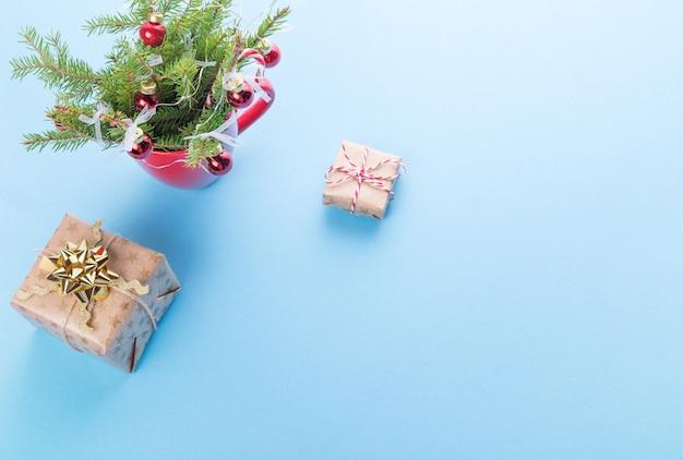 青い背景の上の赤いマグカップのクリスマスの構成、ギフト、クリスマスツリー冬のコンセプト。フラットレイ。