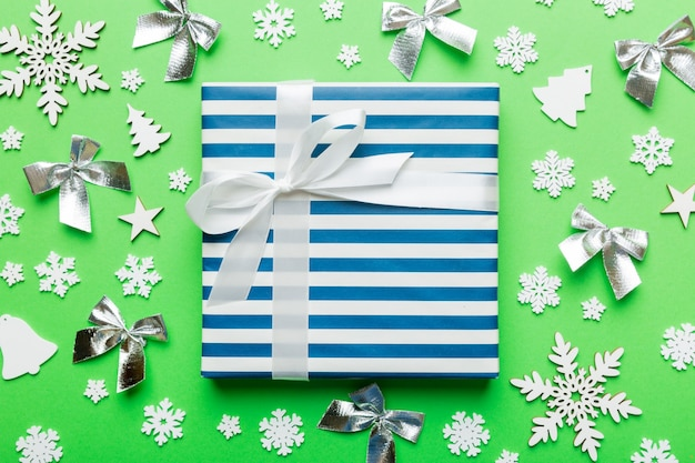 クリスマス作文。色付きの背景に新年の装飾が施されたギフトボックス。クリスマス、冬、新年のコンセプト。フラットレイ、上面図、コピースペース。