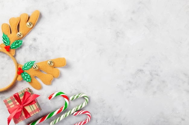 クリスマスの組成物。ギフト、キャラメル杖、コンクリートの灰色の背景に鉢巻きの枝角。冬の休日、正月、クリスマスの概念。上面図。コピースペース