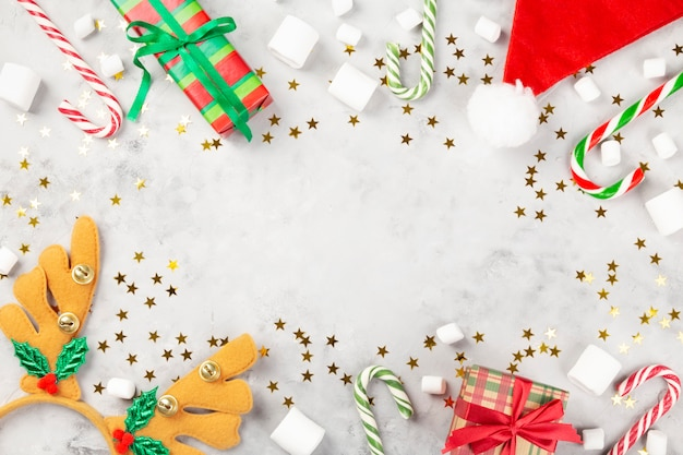Christmas composition. gifts, caramel cane, marshmellow, santa hat, headband antlers on gray concrete background with sparkling stars. concept of winter holidays. top view. copy space