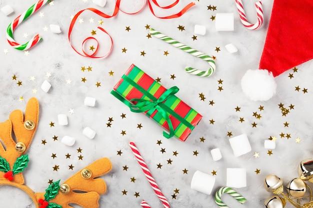クリスマスの組成物。ギフト、キャラメルケイン、マシュマロ、サンタ帽子、輝く星と灰色のコンクリート背景にカチューシャの枝角。冬の休日のコンセプトです。上面図