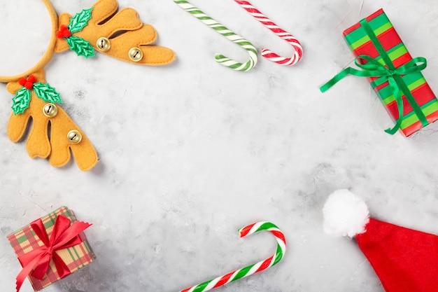 クリスマスの組成物。ギフト、キャラメル杖、サンタ帽子、灰色のコンクリートの背景にカチューシャの枝角。
