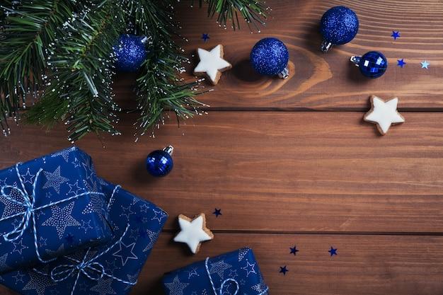 クリスマスの作文。ギフト、モミの木の枝、木の上の青い装飾。クリスマス、冬、年末年始のコンセプト。フラットレイ、上面図、コピースペース