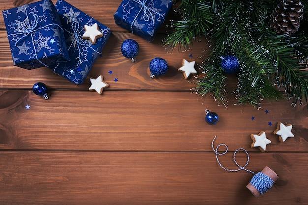 クリスマス作曲。ギフト、モミの木の枝、木の表面の青い装飾。クリスマス、冬、年末年始のコンセプト。フラットレイ、上面図、コピースペース