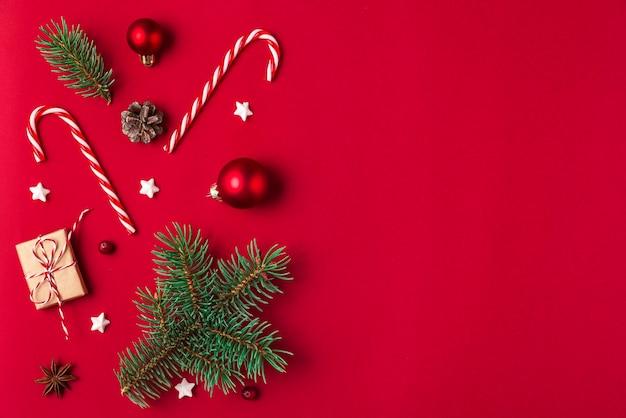 크리스마스 구성. 선물, 전나무 나무 가지, 사탕, 빨간색 배경에 장식. 평평하다