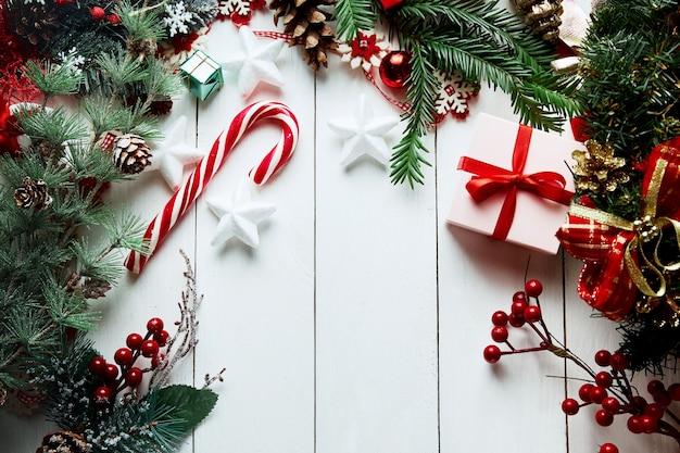 Новогодняя композиция. подарки, еловые ветки, красные украшения на белом фоне. рождество, зима, новогодняя концепция.