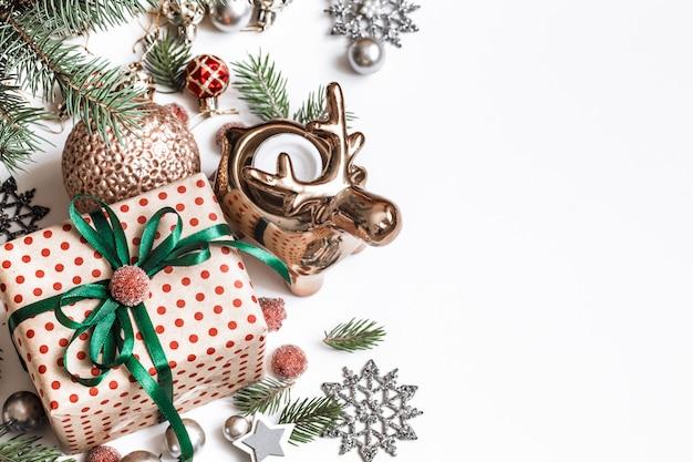 크리스마스 구성. 선물, 전나무 나무 가지, 흰 벽에 붉은 장식. 겨울, 새해 개념입니다. 평평하다, 등각 투영, 텍스트를위한 공간