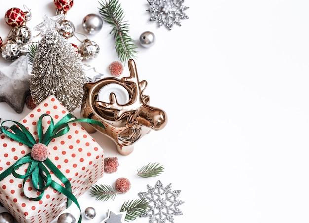 Новогодняя композиция. подарки, ветки ели, красные украшения на белой стене. зима, новогодняя концепция. плоская планировка, изометрия, место для текста
