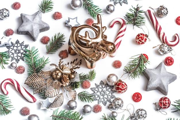 Рождественская композиция. подарки, еловые ветки, красные украшения на белой стене. зима, новогодняя концепция. плоская планировка, изометрическая проекция