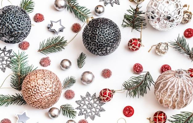 クリスマス作曲。贈り物、モミの木の枝、白い壁に赤い装飾。冬、新年のコンセプト。フラットレイ、アイソメビュー