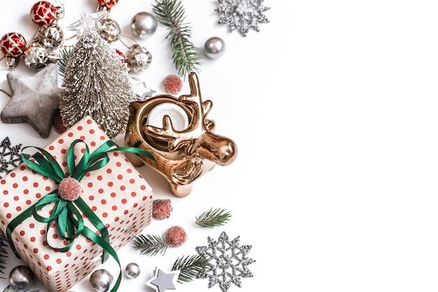 Composizione di natale. regali, rami di abete, decorazioni rosse su fondo bianco.