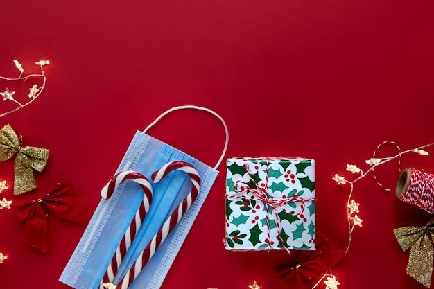 クリスマスの作曲。ギフト、赤い背景に包まれたリボン、ライト、キャンディケインの装飾をプレゼントします。冬、正月フラットレイ、上面図、コピースペース。テンプレートモックアップグリーティングカードのテキストデザイン