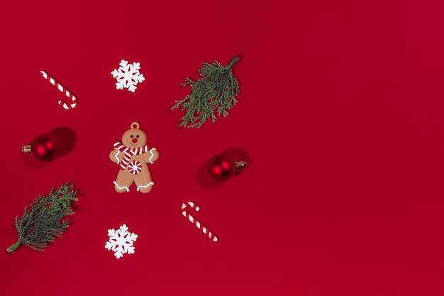 赤い背景の上のクリスマスの構成ジンジャーブレッドマンツリーボールキャンディー新年のセールのコンセプト