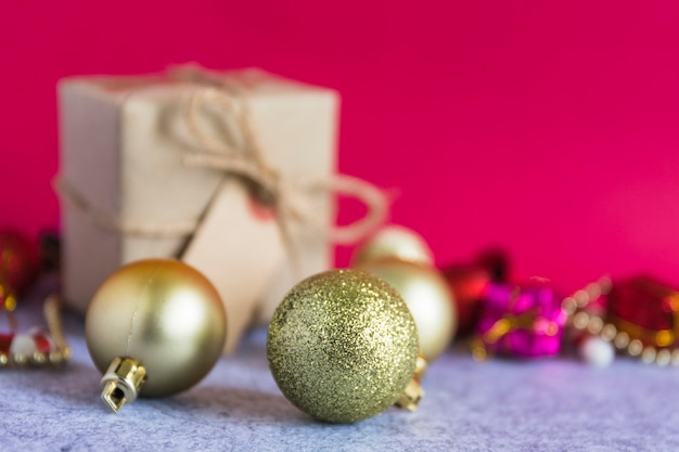 Christmas composition of gold baubles with small gift box