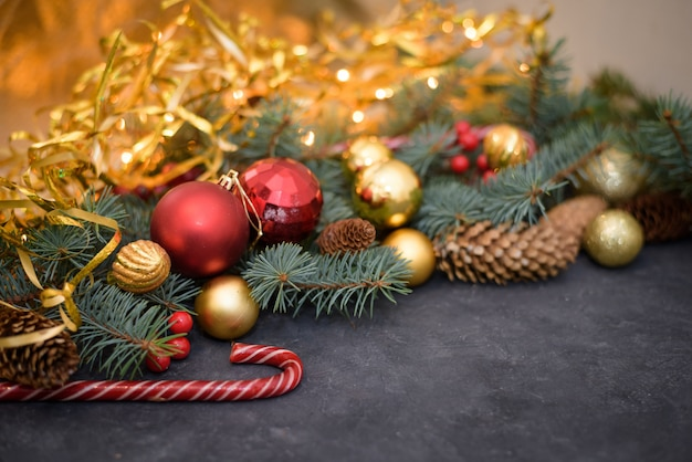Christmas composition of gold and red balls, candy, garlands, fir branches, fir cones.