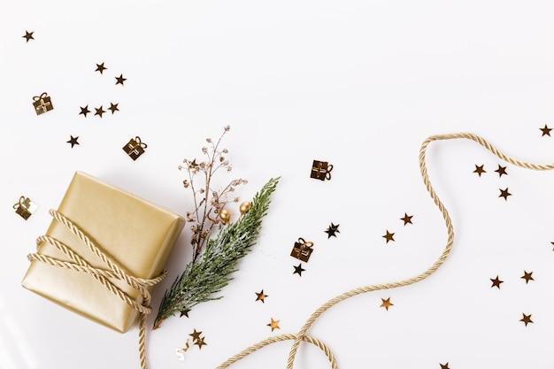 Новогодняя композиция. золотой рождественский подарок, ветви туи и лента. плоская планировка, вид сверху, копия пространства