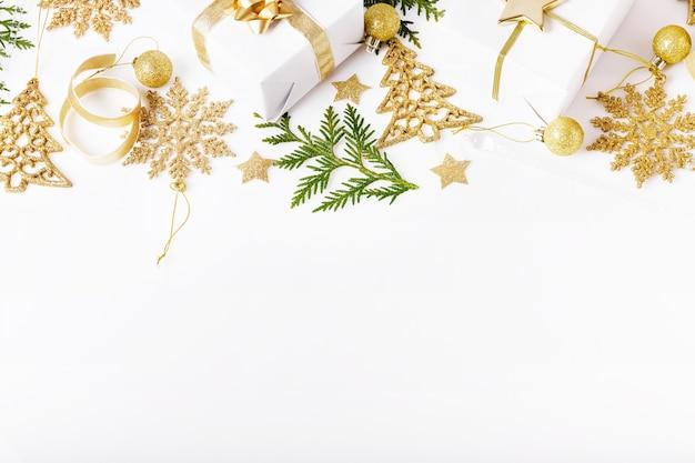 クリスマス作文。ゴールデンクリスマスプレゼント、クロベの枝とリボン。フラットレイ、上面図、コピースペース