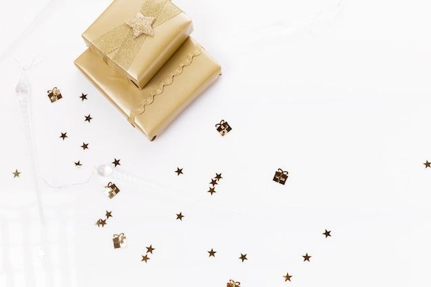 Новогодняя композиция. золотой рождественский подарок, ветви туи и лента. плоская планировка, вид сверху