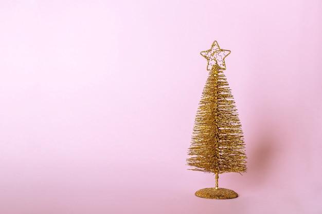 クリスマスの組成物。ピンクのパステル調の背景にキラキラと黄金のクリスマスツリーの装飾