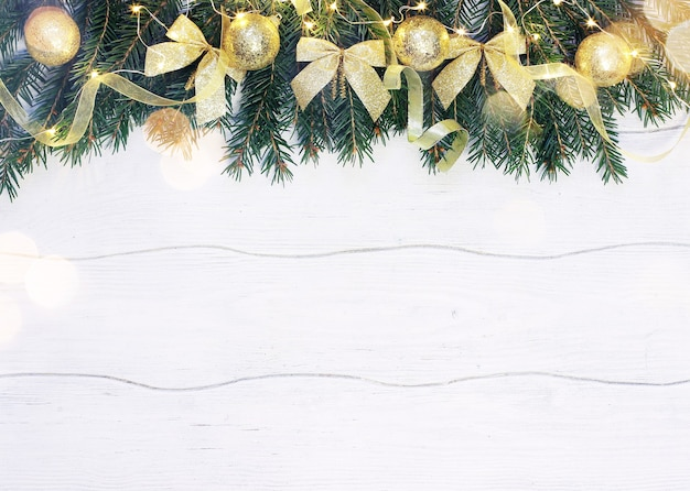 Christmas composition of golden decoration with fir branches on white wooden background