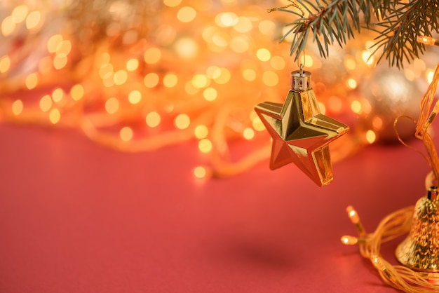 Christmas composition golden star hanging on a spruce branch on a red background