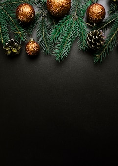 Christmas composition of green fir tree branches with gold baubles