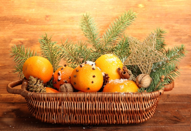 Рождественская композиция в корзине с апельсинами и елкой, на деревянных фоне