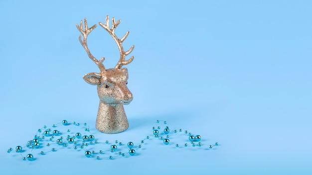 Новогодняя композиция в минималистском стиле - голова золотого оленя на синем фоне с новогодними шарами, огнями. копировать пространство