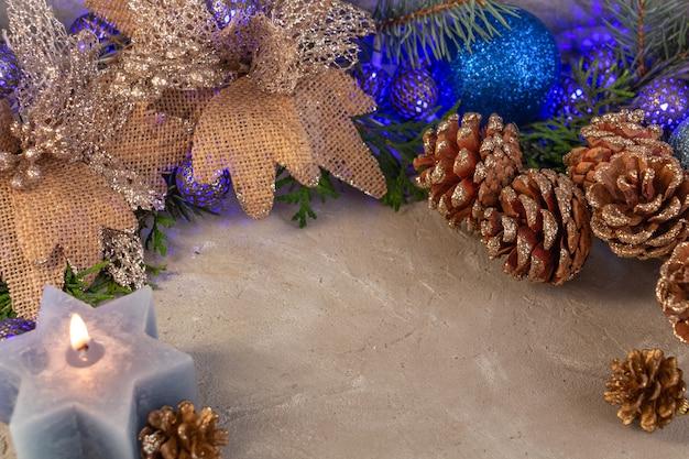 Новогодняя композиция в серебристо-синем цвете гирлянда свеча еловые ветки копией пространства