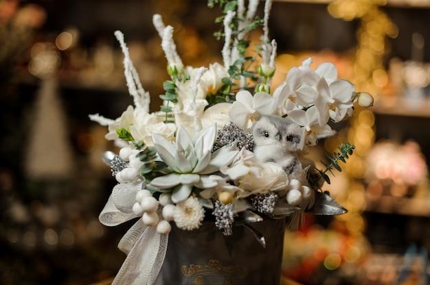 Новогодняя композиция в серой коробке из белых орхидей, суккулентов и разных орнаментов, украшенных бантовой лентой