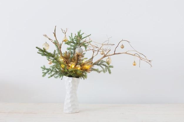 白い背景の上の白い花瓶のクリスマスの構成