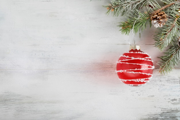 Christmas composition on a light wooden background covered in white snow. christmas  holiday decoration with red ball.  top view. copyspace