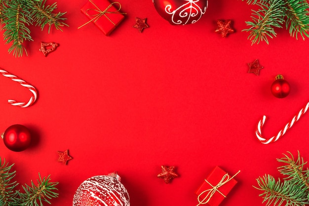 Christmas composition made of fir branches, gift boxes, holiday decorations and candy on red background