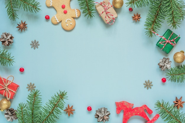 青い背景にモミの木の枝、装飾、ベリー、ジンジャーブレッドで作られたクリスマスの構成