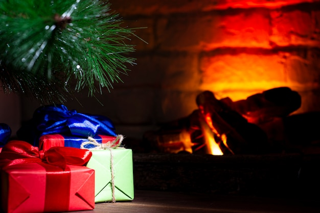 Christmas composition, many colorful gifts under the tree near the burning fireplace, close-up