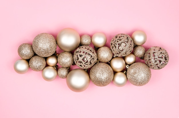 Christmas composition matte gold balls and xmas decorations on a pink background